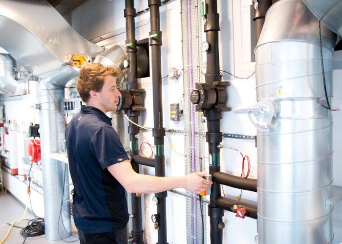 Vvs-energispecialist Mikkel i færd med at regulere en cirkulationspumpe.